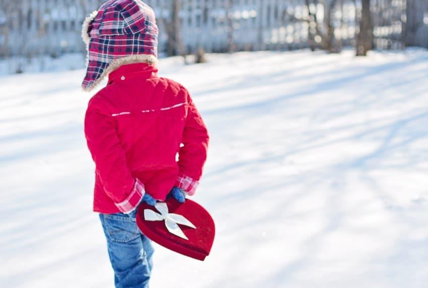 Little boy carrying heart shaped gift